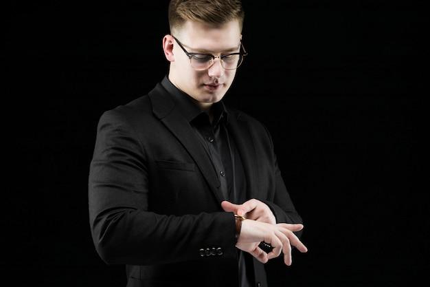 Portret ufny przystojny elegancki odpowiedzialny biznesmen patrzeje zegarki na czerni