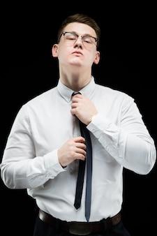 Portret ufny przystojny elegancki odpowiedzialny biznesmen trzyma jego rękę na krawacie