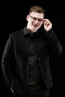 Portret ufny przystojny elegancki odpowiedzialny biznesmen trzyma jego rękę na szkłach