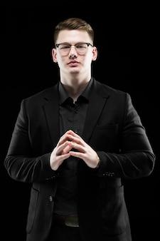 Portret ufny przystojny elegancki odpowiedzialny biznesmen w szkłach z ręki na ręki pozycją