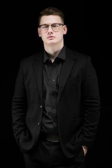 Portret ufny przystojny elegancki odpowiedzialny biznesmen z rękami w kieszeniach na czerni