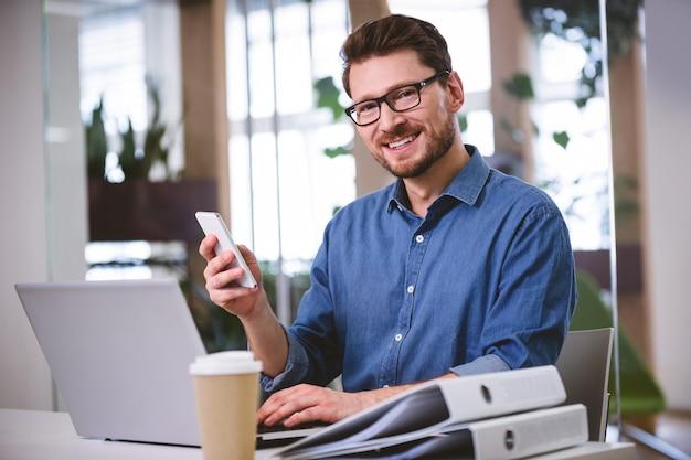 Portret ufny wykonawczy używa telefon komórkowy przy kreatywnie biurem