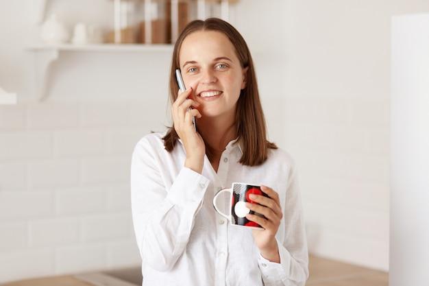 Portret ujmującej kobiety o ciemnych włosach rozmawia przez inteligentny telefon, trzymając kubek w ręce, ciesząc się kawą lub herbatą, mając przyjemną rozmowę, patrząc na kamery.