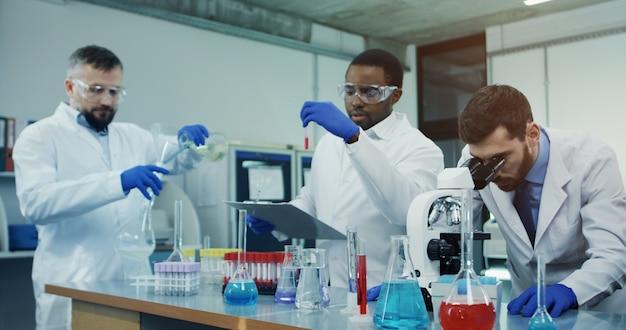 Portret ukazuje naukowca z rasy kaukaskiej, który patrzy w mikroskop podczas badania czegoś w laboratorium, podczas gdy jego współpracownicy z rasy mieszanej rozmawiają na scenie.