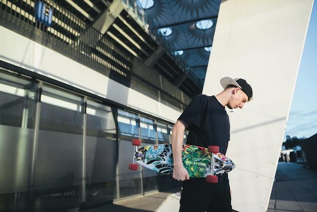 Portret ulicy ubrana nastoletnia łyżwiarka pozująca na tle nowoczesnej architektury.