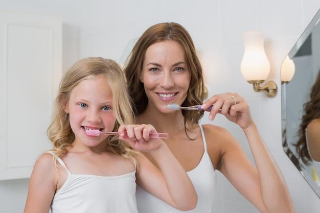Portret up matka i córka szczotkuje zęby