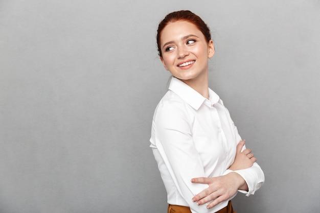Portret uprzejmej rudowłosej bizneswoman 20s w formalnym stroju uśmiecha się i pozuje w biurze na białym tle nad szarym