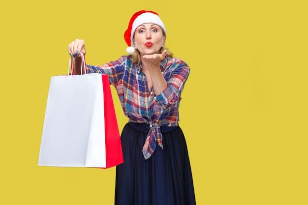 Portret uprzejmie piękna dorosła kobieta w czerwonej czapce mikołaja i stojącej koszuli w kratkę, trzymając torby na zakupy i wysyłając ci pocałunek powietrza, patrząc na kamery. wewnątrz, strzał studyjny, żółte tło