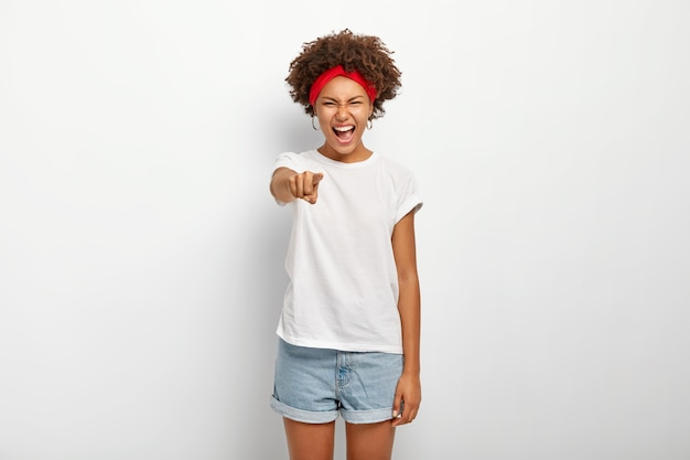 Portret uradowanej afro kobiety śmieje się z czegoś śmiesznego, wskazuje prosto w kamerę, wyraża dobre emocje, nosi czerwoną opaskę, koszulkę i szorty, modelki na białej ścianie.