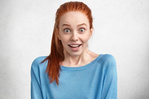 Portret uradowanej ślicznej suki, o zielonych oczach, rudych włosach i piegowatej skórze, czuje zdziwienie i podekscytowanie, dostaje propoas od chłopaka