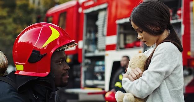 Portret uratowana mała azjatykcia dziewczyna z strażaka mężczyzna stoi blisko samochodu strażackiego. strażak w akcji gaśniczej