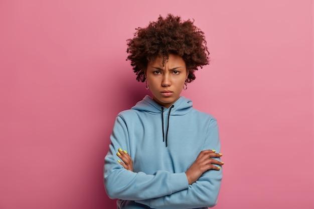 Portret urażonej gniewnej kręconej kobiety ma nieszczęśliwy grymas