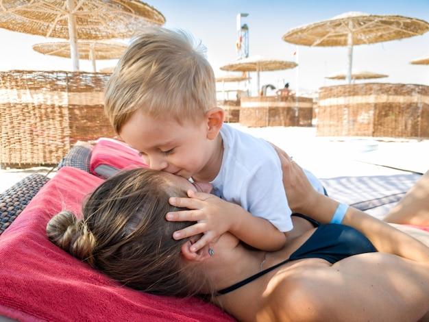 Portret urocza 3 lat maluch chłopiec całuje matkę relaks na plaży pod parasolem. rodzinny relaks i dobra zabawa na plaży podczas letnich wakacji