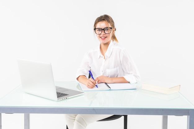 Portret urocza biznesowa kobieta pracuje przy jej biurkiem z papierkową robotą odizolowywającymi na białym tle i laptopem