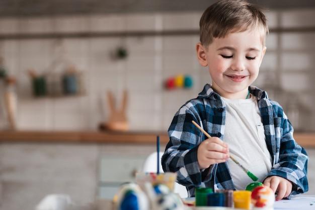 Portret urocza chłopiec maluje jajka dla easter