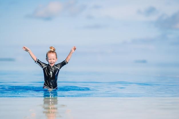 Portret urocza mała dziewczynka przy plażą podczas wakacje