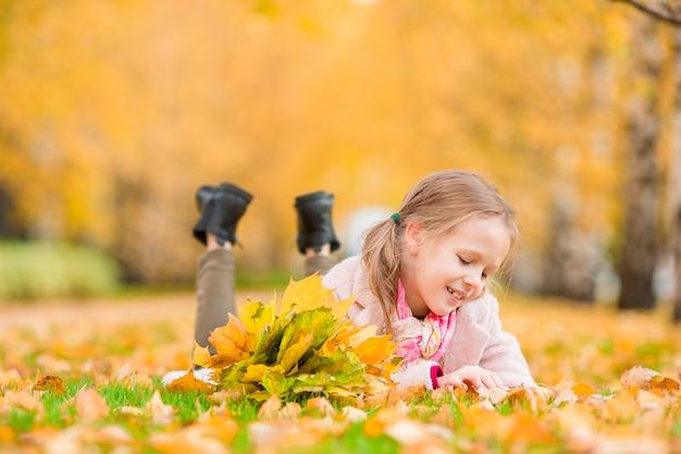 Portret urocza mała dziewczynka z kolorem żółtym opuszcza bukiet w spadku