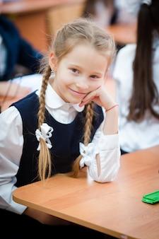 Portret urocza mała szkolna dziewczyna w sala lekcyjnej