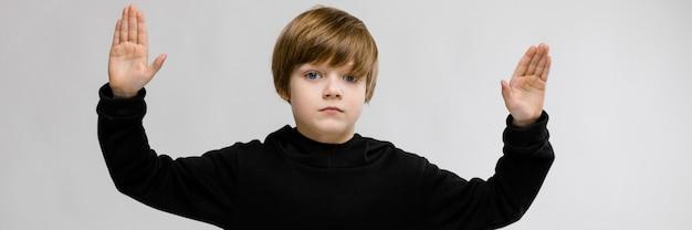 Portret urocza poważna chłopiec pozycja z rękami up na szarości ścianie
