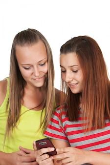 Portret urocze młode kobiety używa telefon komórkowego wpólnie odizolowywającego na bielu