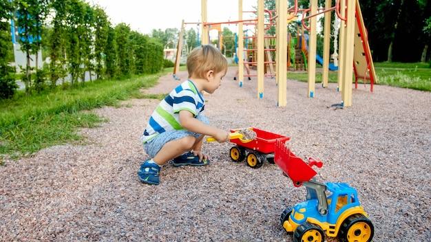 Portret uroczego 3-letniego chłopca bawiącego się zabawkową ciężarówką z przyczepą na placu zabaw w parku
