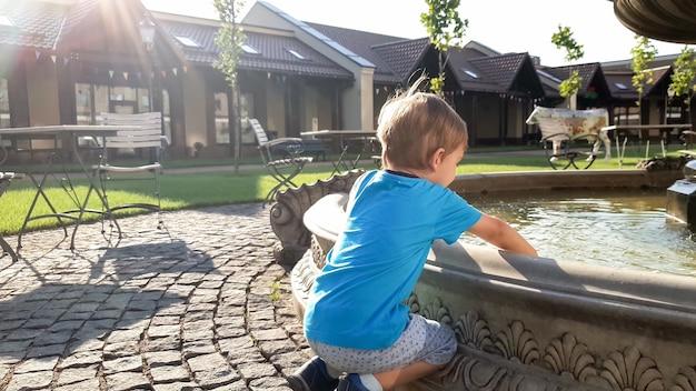 Portret uroczego 3-letniego chłopca dotykającego wody w fontannie w parku