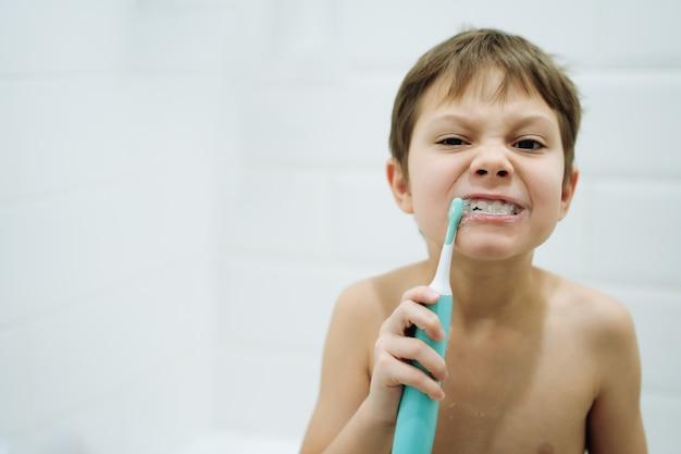 Portret uroczego 6-letniego chłopca szczotkującego zęby szczoteczką elektryczną w łazience