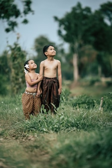 Portret uroczego azjatyckiego chłopca bez koszuli i dziewczyny w tajskim tradycyjnym stroju i położył piękny kwiat na uchu, stojąc ręka w rękę i patrząc na niebo z uśmiechem, kopiując przestrzeń