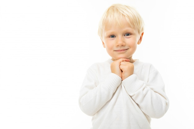 Portret uroczego blond chłopca w białej koszulce na białej ścianie