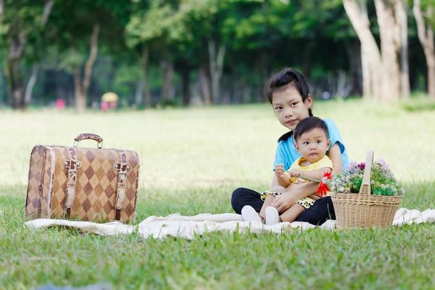 Portret uroczego brata i siostry uśmiech i przytulanie siedzi w parku.