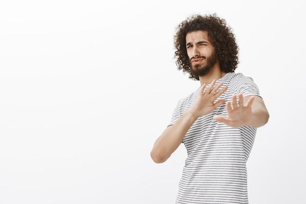Portret uroczego brodatego, dumnego faceta w modnym stroju, pochylającego się do tyłu i wyciągającego dłonie w kierunku, broniącego przed czymś okropnym, wyrażającego niechęć i niechęć