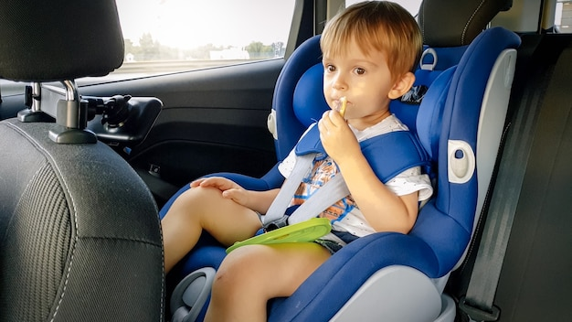 Portret uroczego chłopca siedzącego w foteliku samochodowym i jedzącego ciasteczka