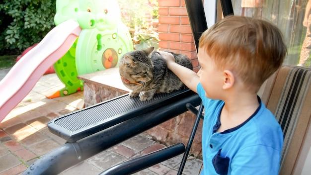 Portret uroczego chłopca z kotem siedzącym na ławce huśtawki w ogrodzie przydomowym domu