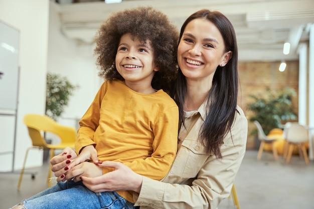 Portret uroczego chłopca z włosami afro, uśmiechającego się podczas pozowania do kamery razem z