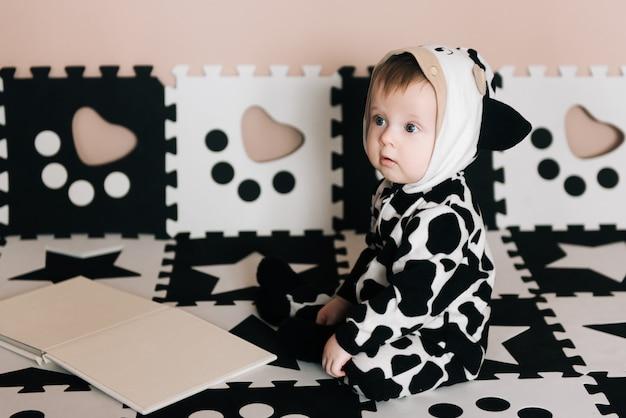 Portret uroczego cute baby. chłopiec w czarno-białym garniturze siedzi i ogląda książkę w domu