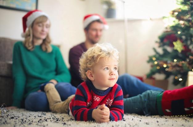 Portret uroczego dzieciaka, siedzącego na dywanie z rodzicami, cieszącego się świętami bożego narodzenia