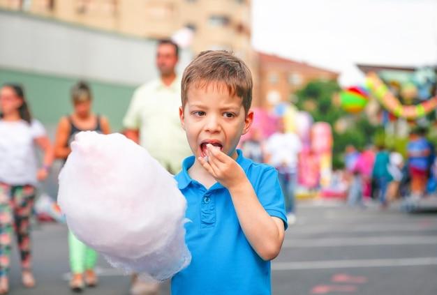 Portret uroczego dziecka jedzącego watę cukrową na tle festiwalu letnich targów