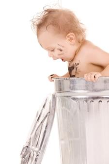 Portret uroczego dziecka w koszu na śmieci