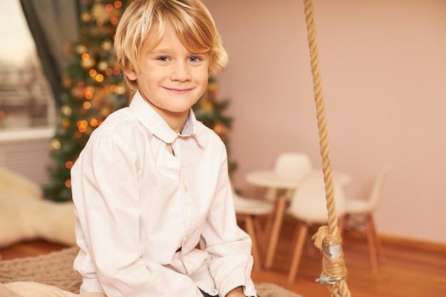 Portret uroczego europejskiego chłopca w białej koszuli cieszącego się świątecznym nastrojem, przewidującego wigilię bożego narodzenia, siedzącego w salonie z udekorowanym drzewkiem noworocznym, uśmiechającego się radośnie