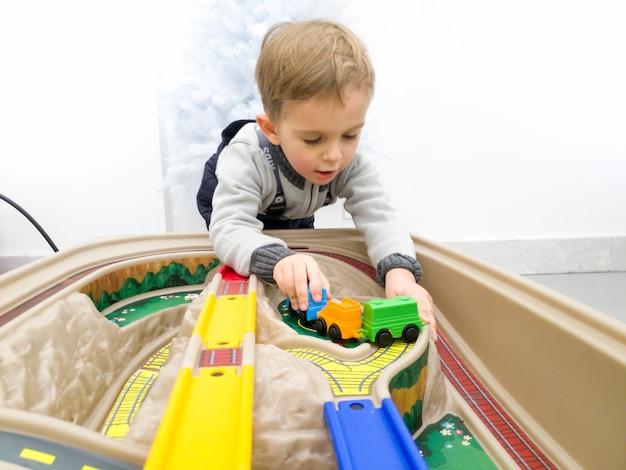 Portret uroczego małego chłopca bawiącego się kolorowymi plastikowymi zabawkami pociągów