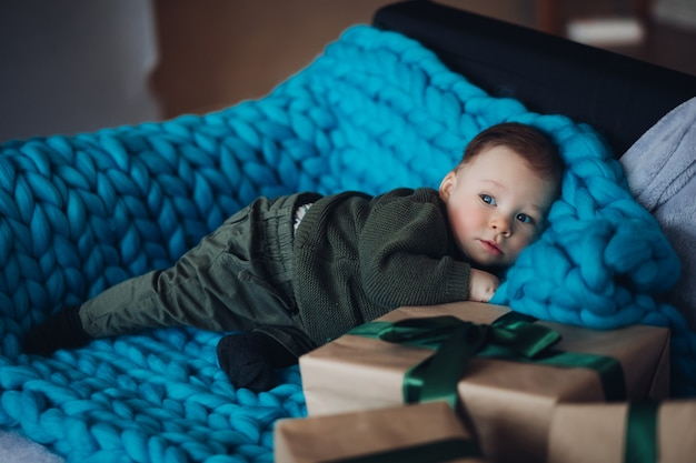 Portret uroczego małego chłopca w ubraniach khaki relaksującego na niebieskim kocu z dzianiny z zapakowanymi prezentami świątecznymi obok niego