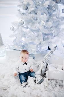 Portret uroczego małego dziecka na sobie białą bluzkę i uśmiechnięte z przodu siedzi na sztucznym śniegu w pobliżu choinki