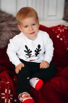 Portret uroczego małego dziecka na sobie sweter z boże narodzenie jelenia i uśmiechnięte z przodu siedzi w sztucznym śniegu na choince