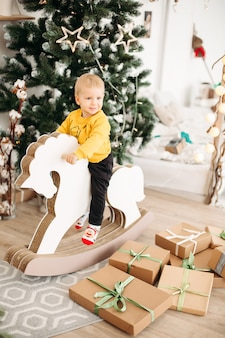 Portret uroczego małego dziecka na sobie sweter z bożonarodzeniowym jeleniem i uśmiechnięte z przodu siedzi na koniu na biegunach na choinkę