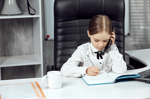 Portret uroczego małego dziecka przedstawiającego szefa agencji przy białym stole
