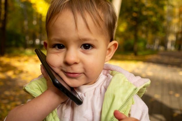 Portret uroczego malucha bawiącego się w rozmowie na smartfonie