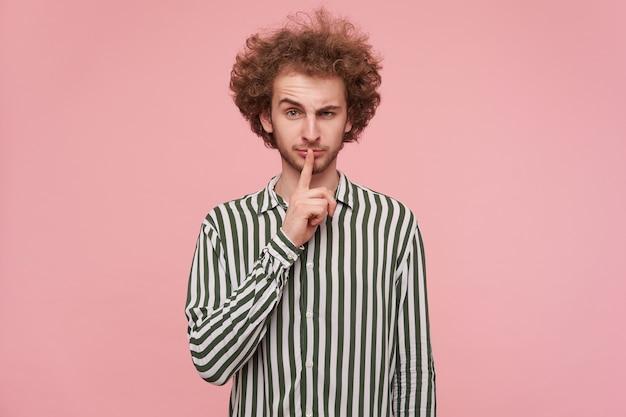 Portret uroczego młodego kręconego rudowłosego mężczyzny ubranego w zwykłe ubrania, trzymając palec wskazujący na ustach, patrząc na kamerę z uniesioną brwią, stojącego na różowej ścianie