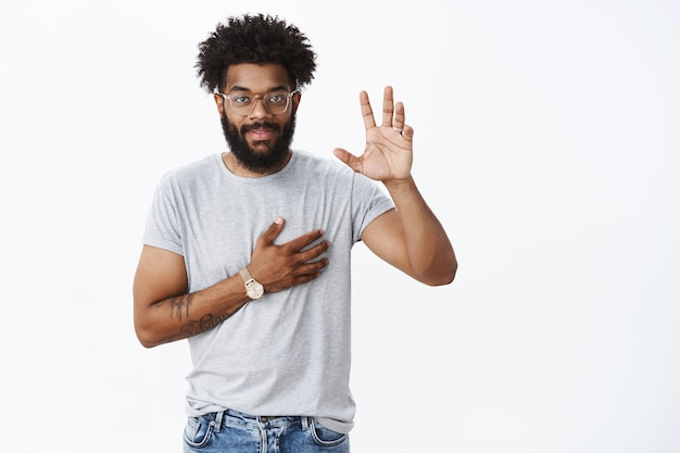Portret uroczego, pewnego siebie, uśmiechniętego afroamerykanina, który obiecuje, podnosząc rękę i trzymając rękę na sercu, składając przysięgę lub przysięgę, przysięgając, że nie leży na szarej ścianie