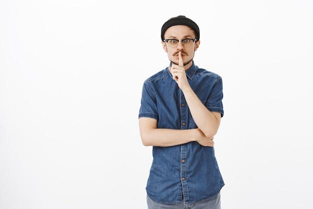 Portret uroczego, przyjaźnie wyglądającego, nerwowego europejczyka w okularach i czarnej czapce wykonującego gest uciszenia z palcem wskazującym na ustach i uniesionymi brwiami, prosząc o zachowanie tajemnicy