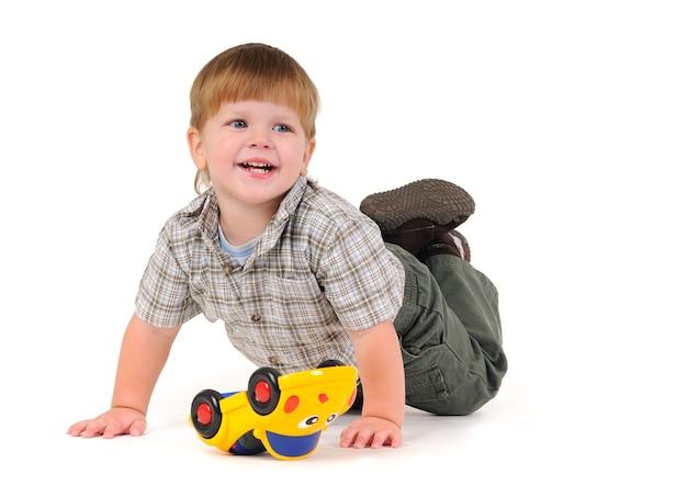 Portret uroczego uśmiechniętego chłopca bawiącego się na podłodze z żółtym samochodem na białej ścianie. koncepcja gry dla dzieci w wieku przedszkolnym i dzieci. przestrzeń reklamowa
